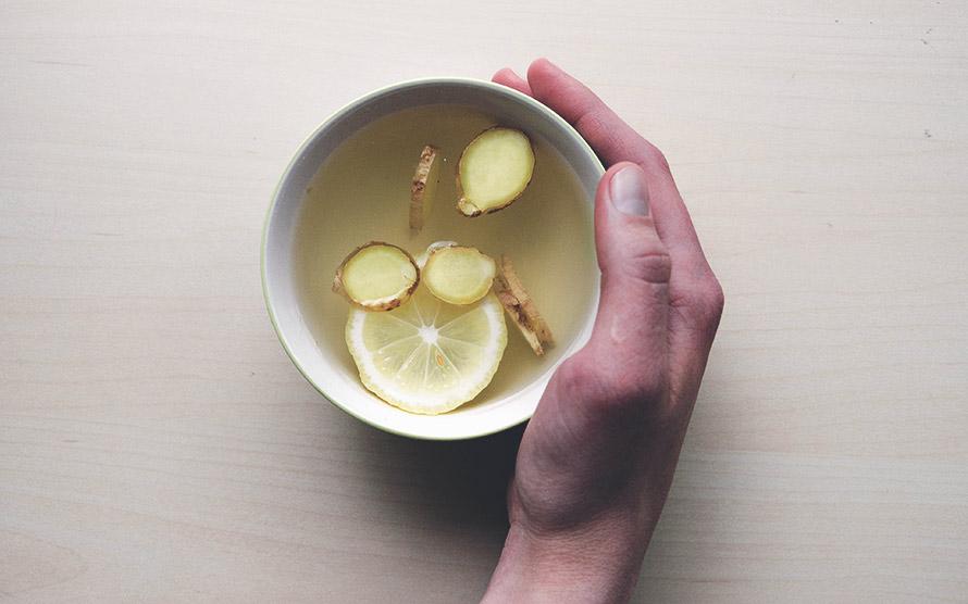 Bild på en hand som håller en kopp med ingefära-te